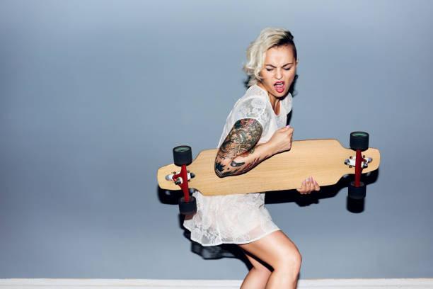 blonde mädchen herumalbern mit longboard - lausbub tattoo stock-fotos und bilder