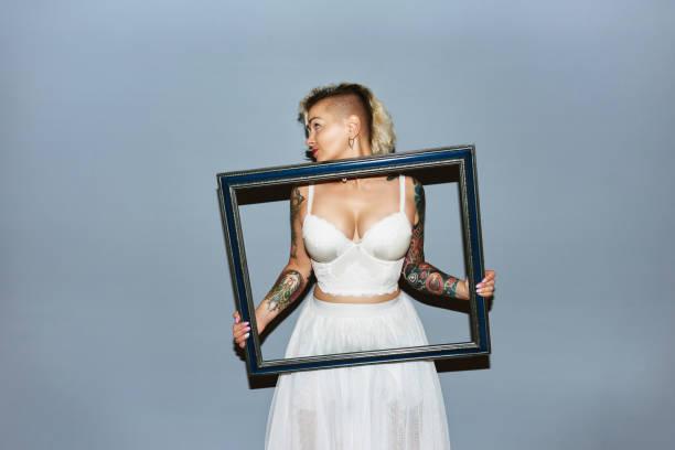 blonde mädchen goofing rund um - lausbub tattoo stock-fotos und bilder