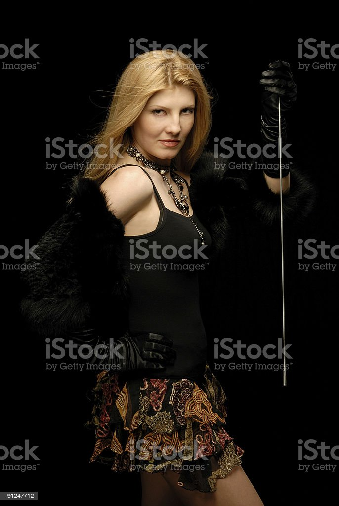 Blond girl in fancy clothes holding up the horsewhip royalty-free stock photo