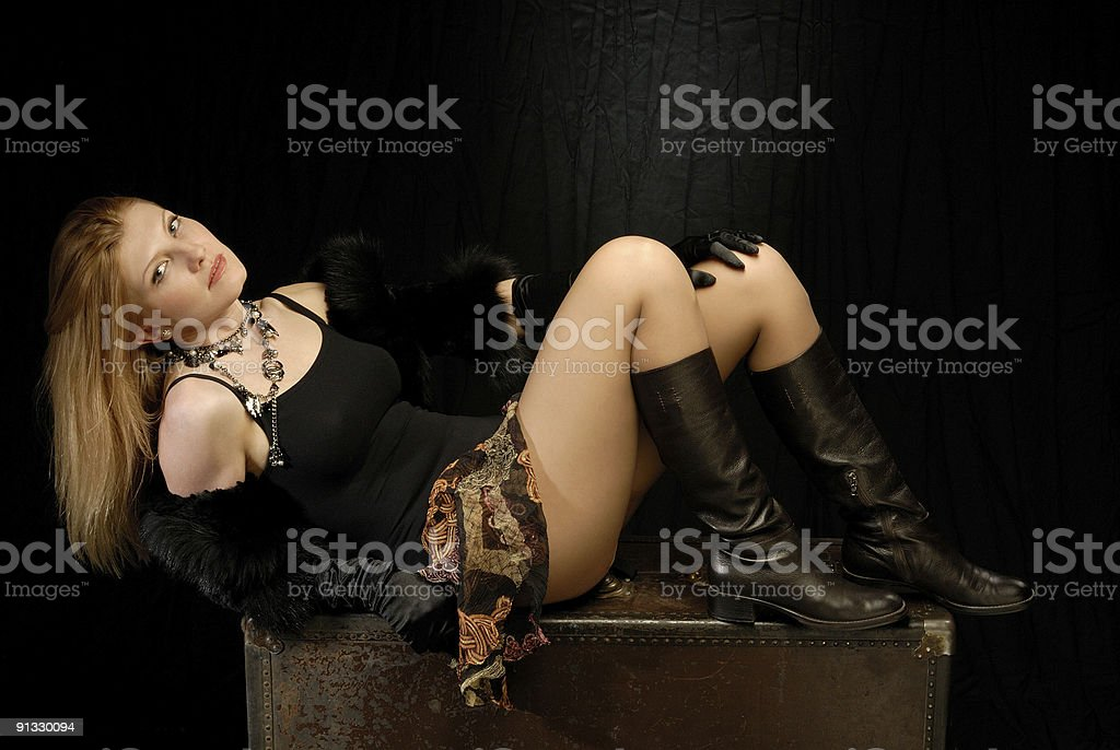 Blond girl in fancy clothes laying on old leather trunk royalty-free stock photo