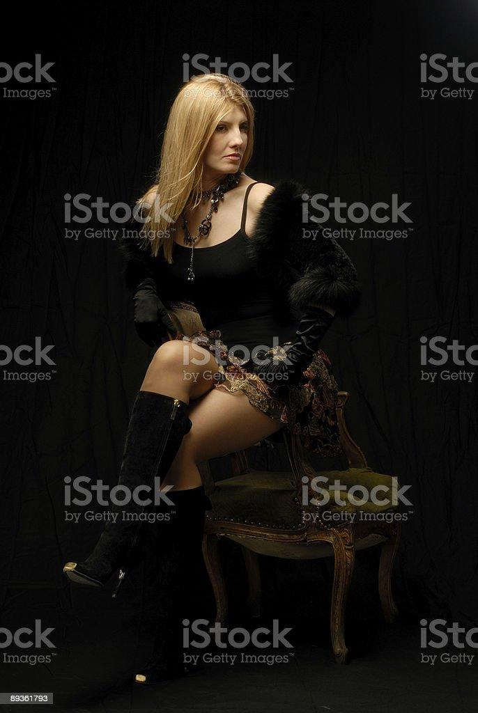 Capelli biondi donna in vestiti alla moda in poltrona guardando lontano foto stock royalty-free