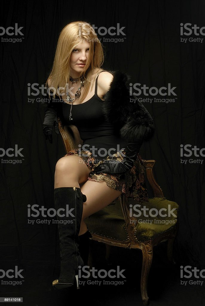 Blond girl in fashionable clothes sitting on arm of armchair royalty-free stock photo