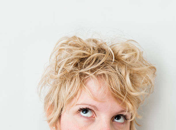 blond girl looking up / left (mixed hairs) - messy hair stock photos and pictures