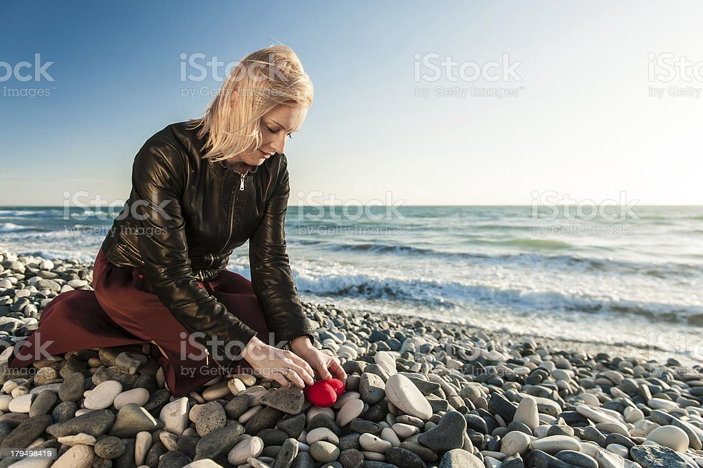 Blond Girl on the seaside hiding a heart royalty-free stock photo