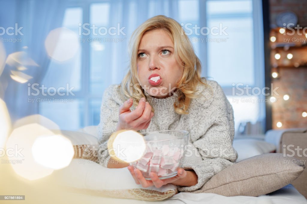 Blond girl relaxing in apartment with delicious dessert stock photo