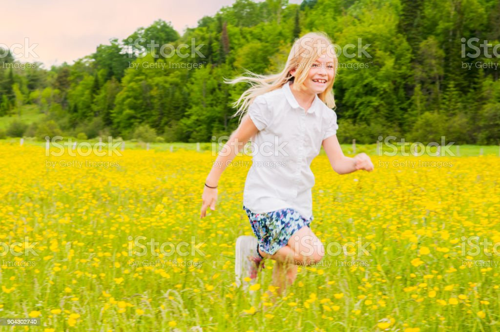 Blond girl running at sunset in a yellow field stock photo