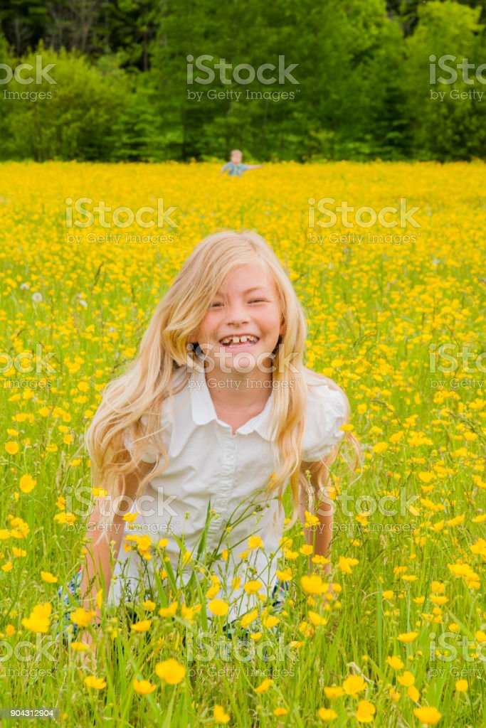 Blond girl smiling in a yellow field stock photo