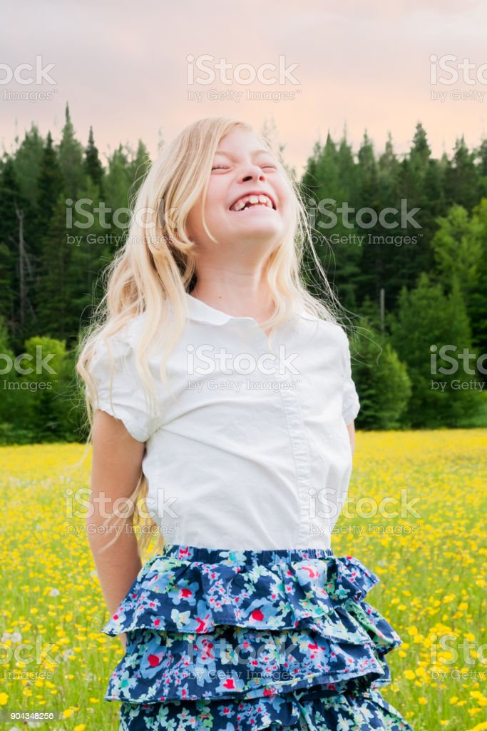 Blond girl smiling to the sky at sunset in a yellow field stock photo