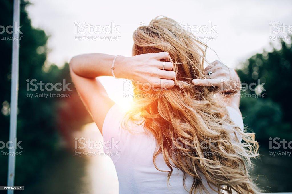 Blond girl standing at the bridge stock photo