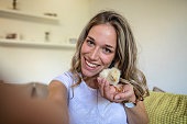 Gorgeous blond girl sitting on a couch and playing with her little chick