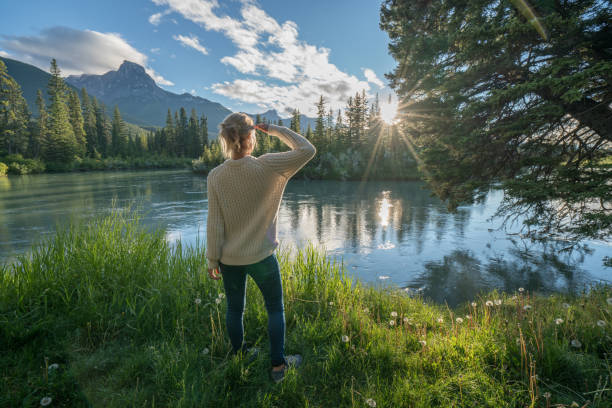 Blond girl watching sunrise from river bank stock photo