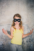 blond girl with black superhero mask and yellow shirt is posing in front of concrete background
