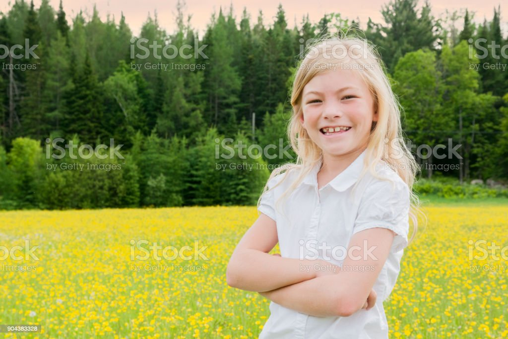 Blond girl's portrait smiling at sunset in a yellow field stock photo