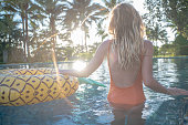 Young woman on vacations enjoying swimming pool with inflatable pineapple relaxing with beautiful light and palm trees in tropical scenery. People travel holiday in exotic places concept