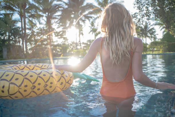 Blondes Haar Mädchen entspannen im Pool bei Sonnenuntergang Holding aufblasbaren Ring Ananas – Foto