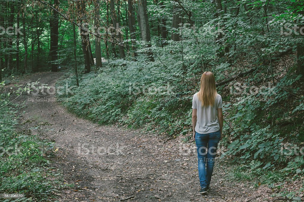 Blond hair girl walking by curvy road in the forest stock photo