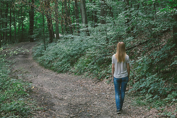 blond hair girl walking by curvy road in the forest - beautiful curvy girls stock photos and pictures