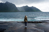 Blond hair girl with a backpack stands on big stones near the water and looks at the ocean. Waves, splashing. Enjoy the moment, relaxation. Wanderlust. Travel, adventure, lifestyle. Explore Norway
