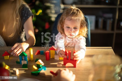 Blond hair toddler girl playing with toy blocks at home, sitting at dining table, unrecognizable people