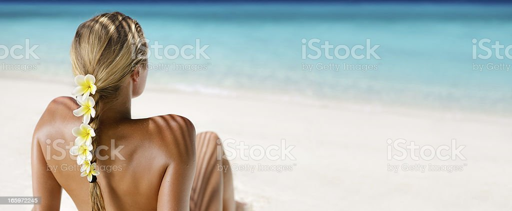 blond hair woman with yellow plumeria sunbathing at a beach stock photo