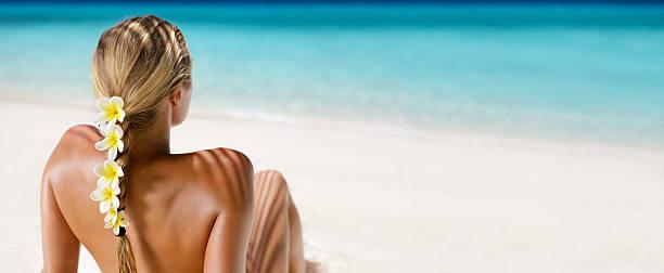 blond hair woman with yellow plumeria sunbathing at a beach stock photo