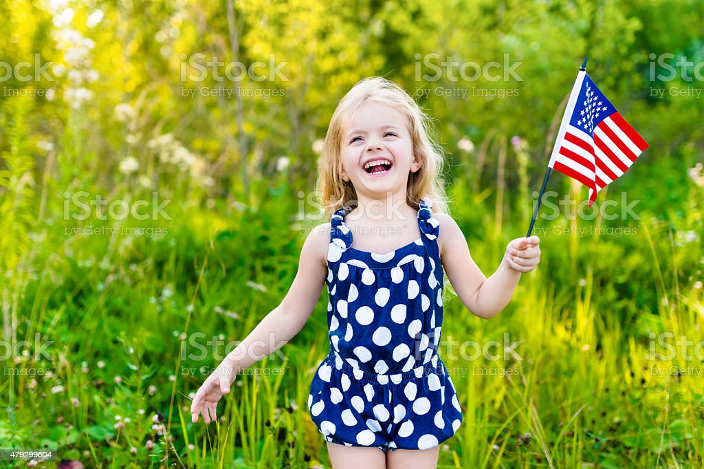 Blond little girl holding american flag, waving it and laughing stock photo