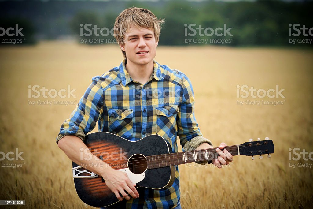 Blond man in checkered shirt playing guitar in country field royalty-free stock photo