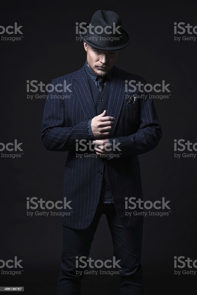 Blond man with fedora and navy suit on black background stock photo