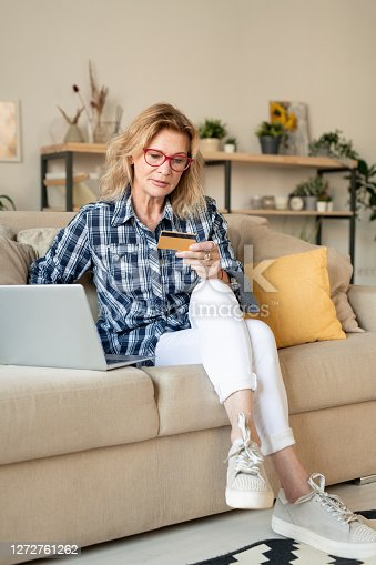 Blond mature female looking at credit card while sitting on couch in front of laptop in living-room and going to pay for online goods