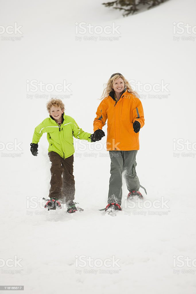 Blond Mother and Son Snowshoeing In Powder Snow royalty-free stock photo