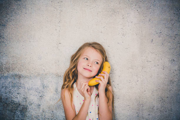 blonde, hübsche Mädchen tut Anruf mit einer Banane im studio – Foto