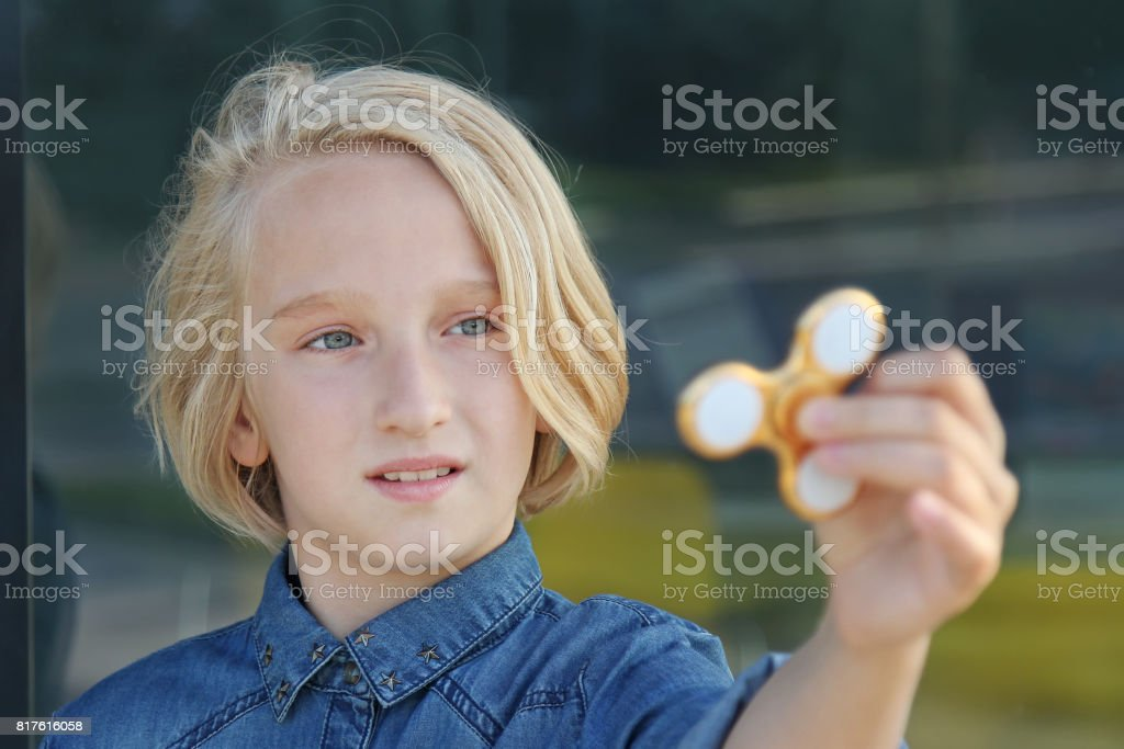 Blond school aged girl playing with a gold fidget spinner. A popular trendy toy. stock photo