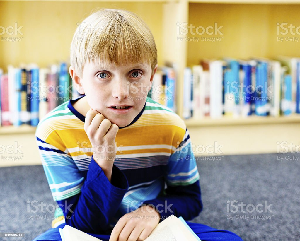 Blond schoolboy looks up from his book in the library royalty-free stock photo