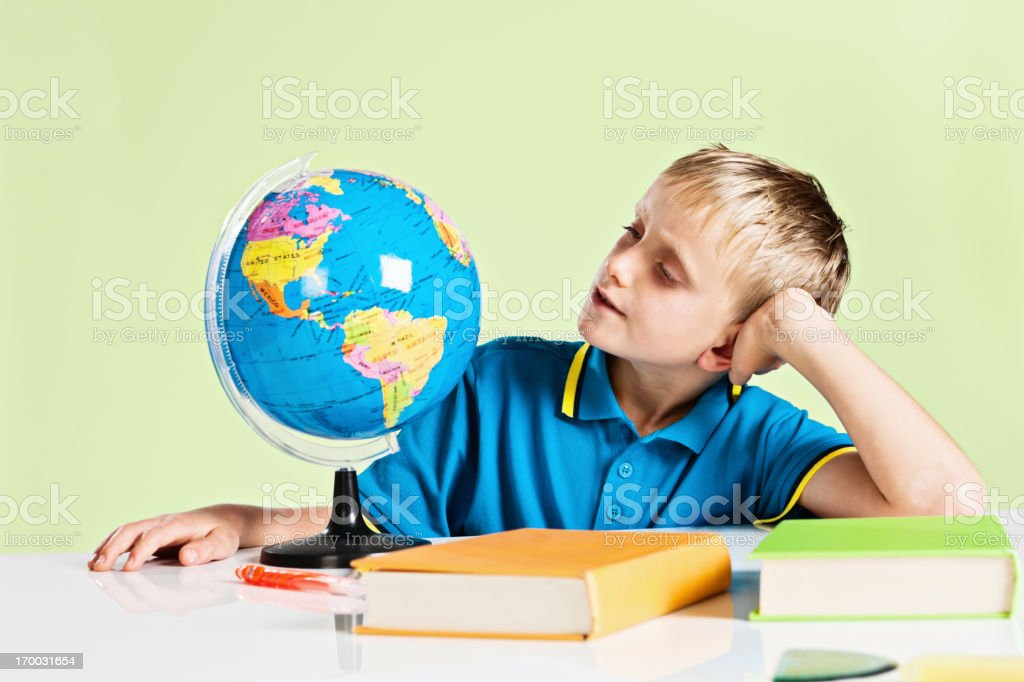 Blond schoolboy studying geography on world globe royalty-free stock photo