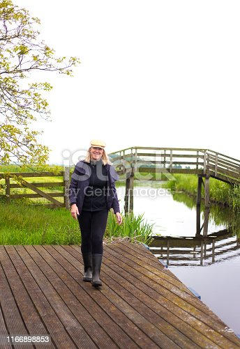 A smiling blond senior woman in rubber boots walks on a dock near a canal with an old wooden bridge in the background. Copy space available in the white sky.