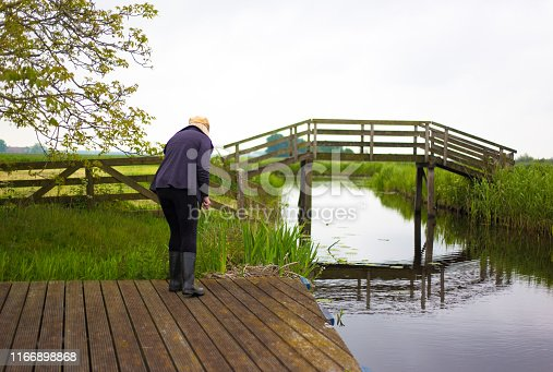 A blond senior woman in rubber boots on a dock near a canal with an old wooden bridge in the background. Copy space available in the white sky.