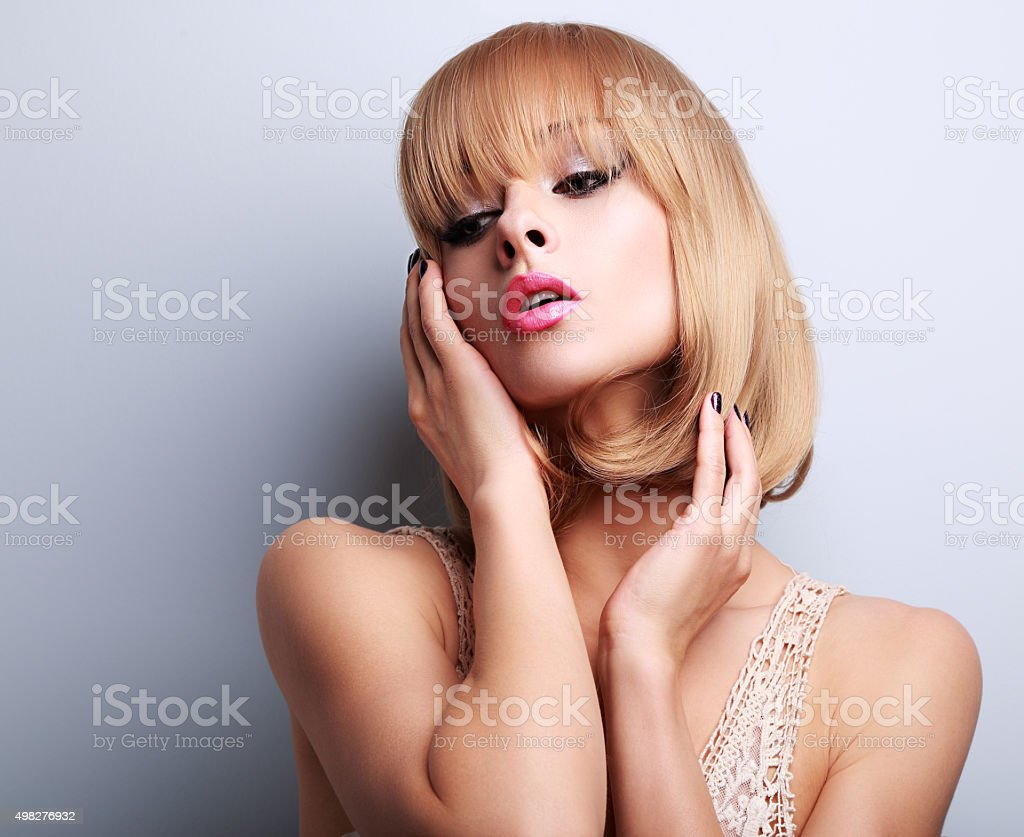 Blond short hair style woman with pink lipstick posing stock photo