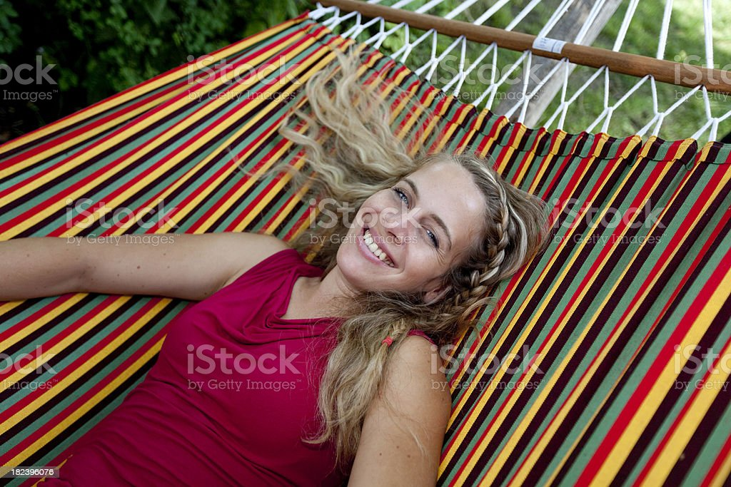 Blond smiling girl in a colourful hammock stock photo