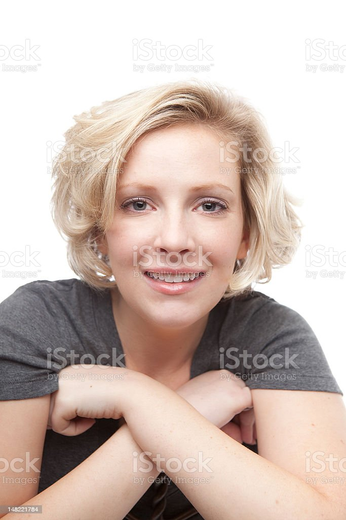 Blond smiling young woman in gray shirt on white stock photo