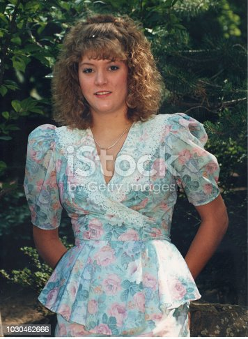 Outdoor picture of a blond teen girl wearing a pink and blue dress in the summer