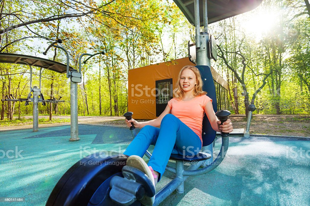 Blond teenage girl cycling on exercise equipment stock photo