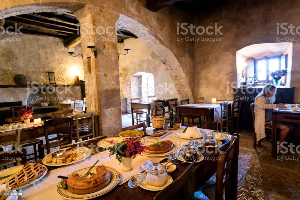 Blond teenage girl eats breakfast in the ancient arched dining room in the diffused hotel of Santo Stefano di Sextantio, in the medieval fortified village of Santo Stefano di Sessanio; Gran Sasso National Park; L'Aquila Province, Abruzzo; Italy; Europe – zdjęcie