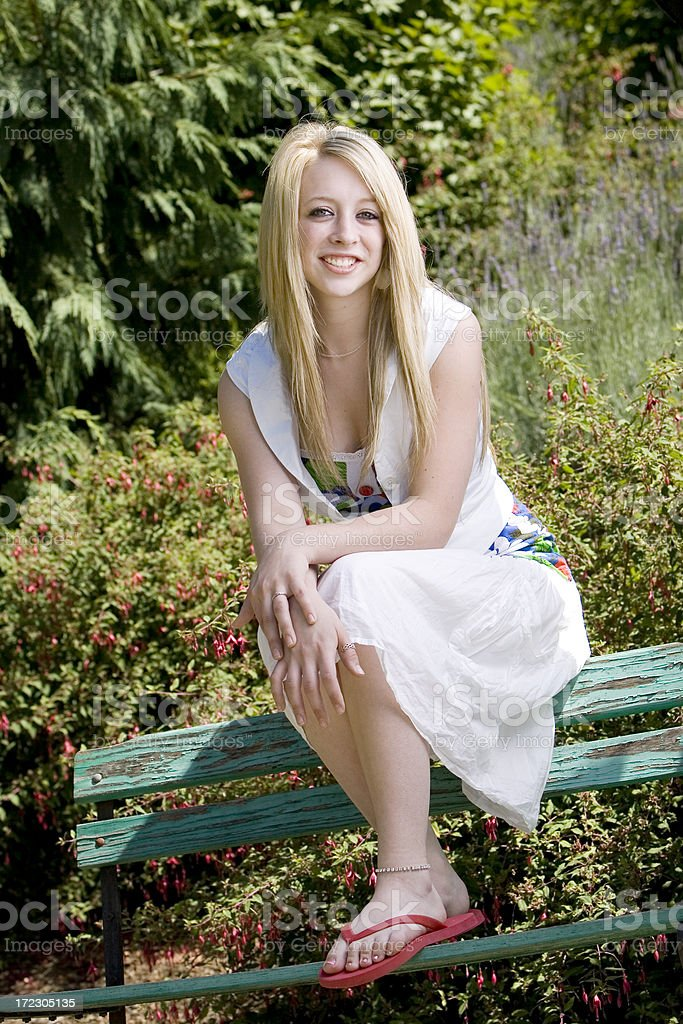 Blond Teenage Girl Smiling Outside On Park Bench Copy -5418