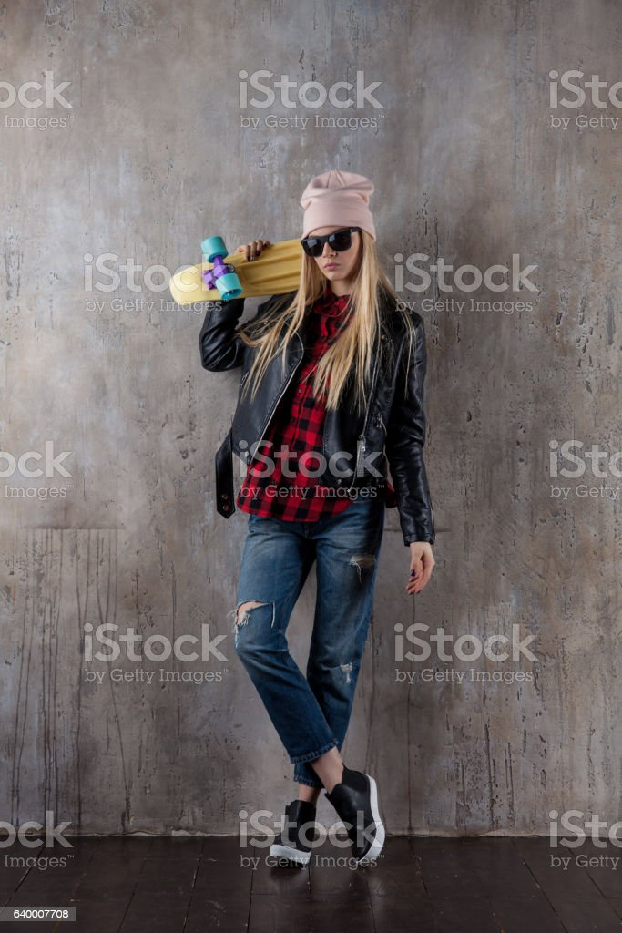 Blond teenager girl in black sunglasses and pink hat with stock photo