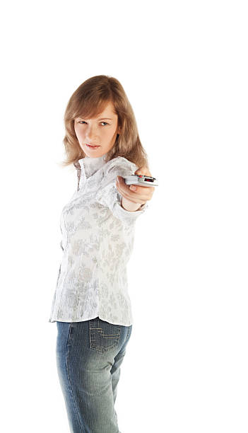 Blond woman aiming TV remote stock photo