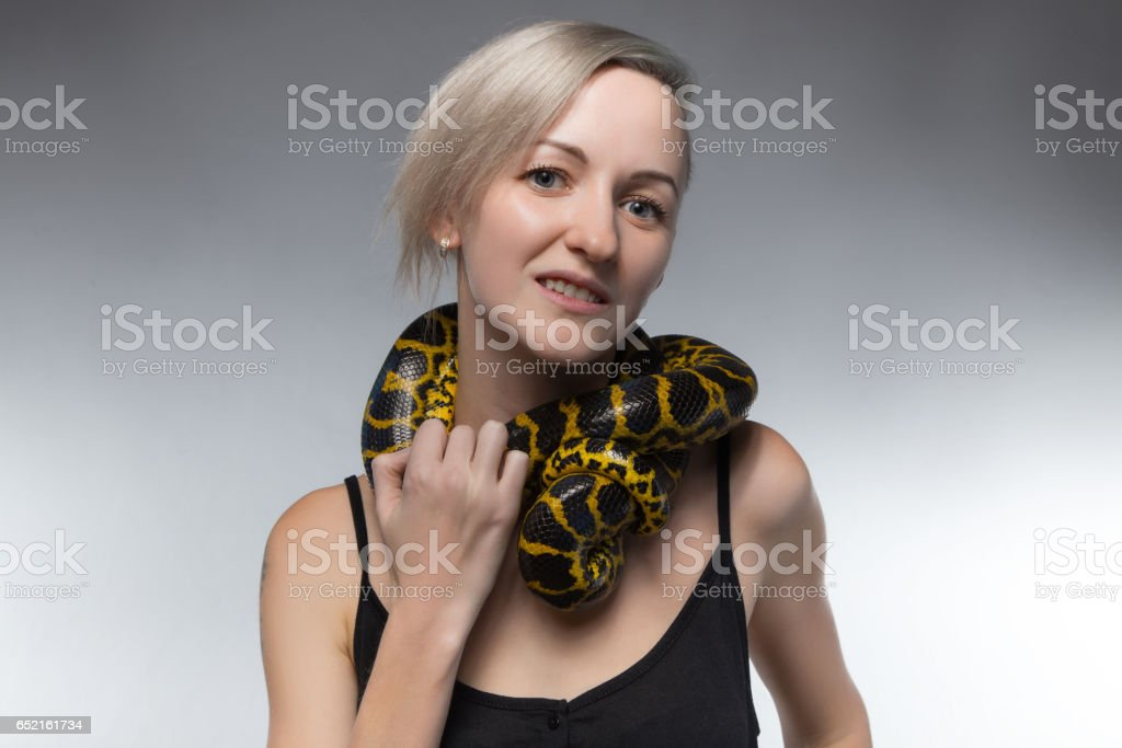 Blond woman and strangling snake stock photo