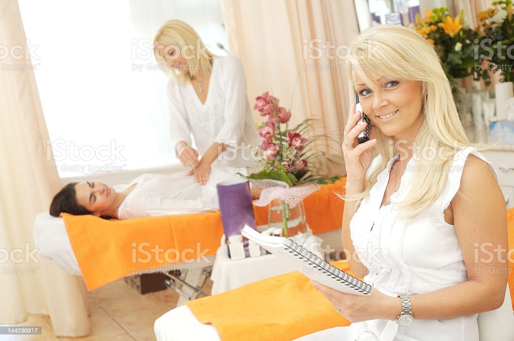 Blond woman beauty salon worker on phone with spiral book stock photo