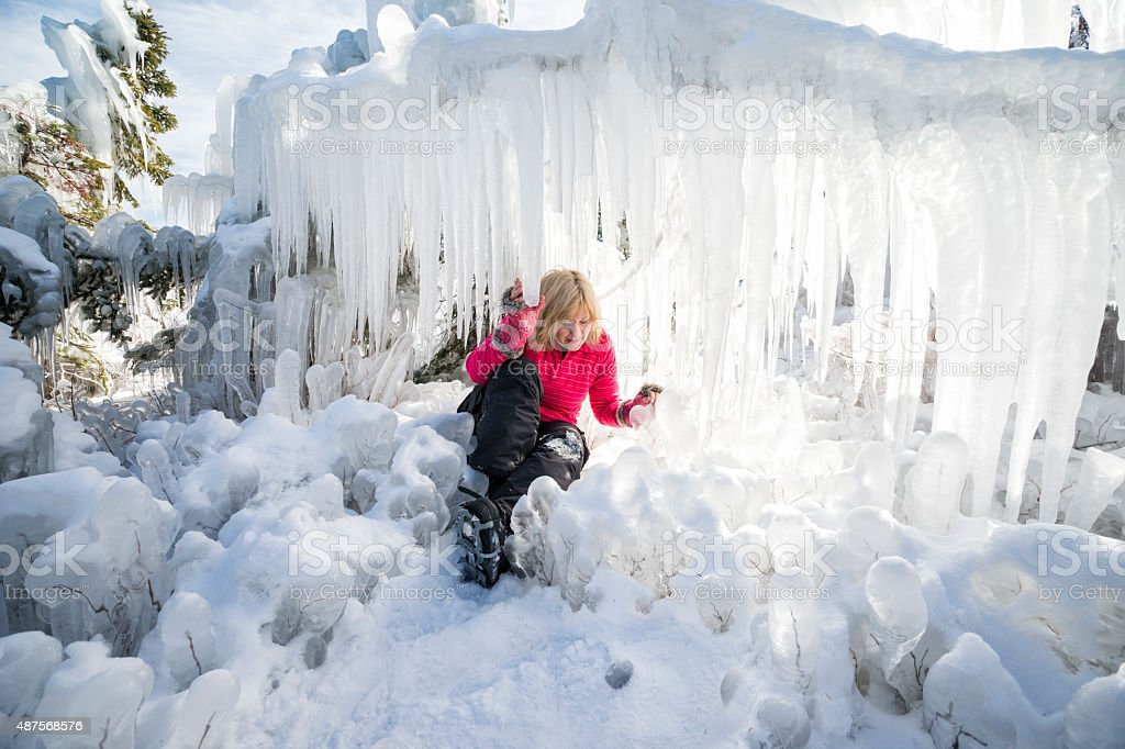 Blond woman carefully crawls around icicles stock photo
