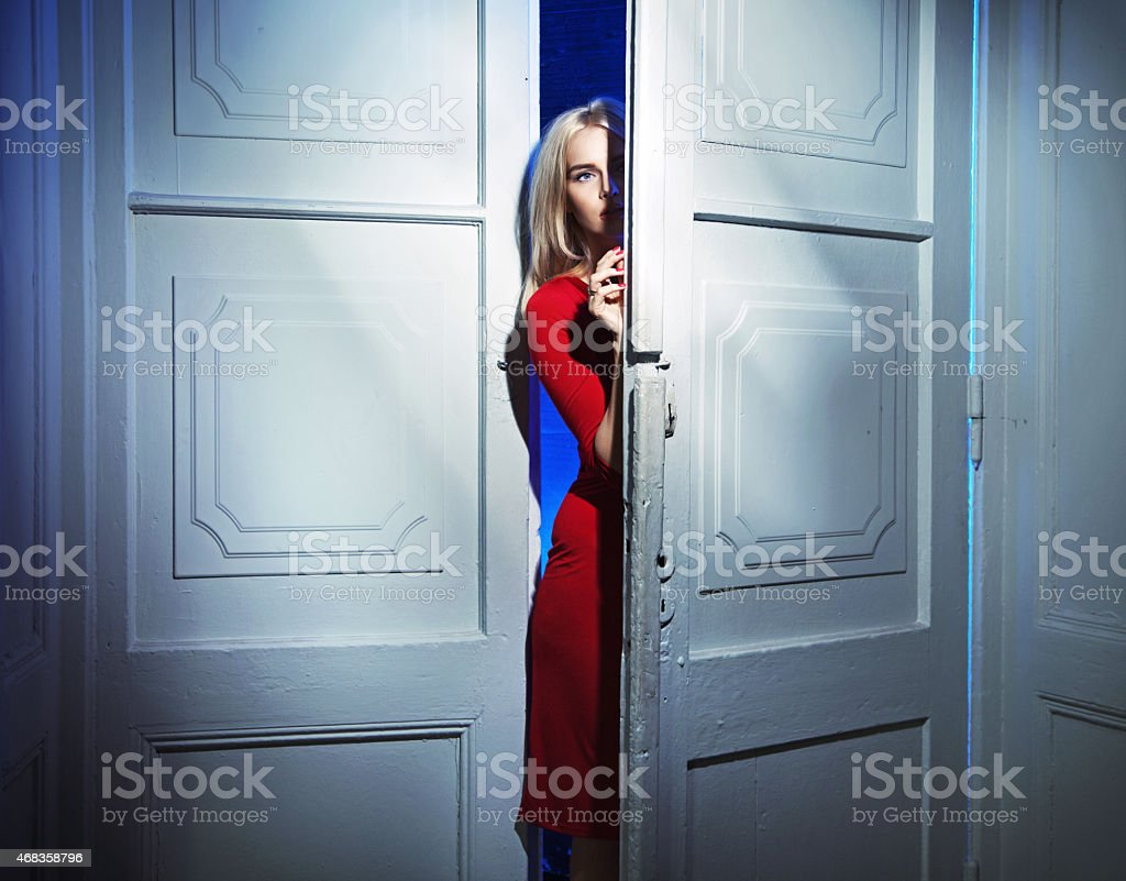 Blond woman carefully opening the door royalty-free stock photo