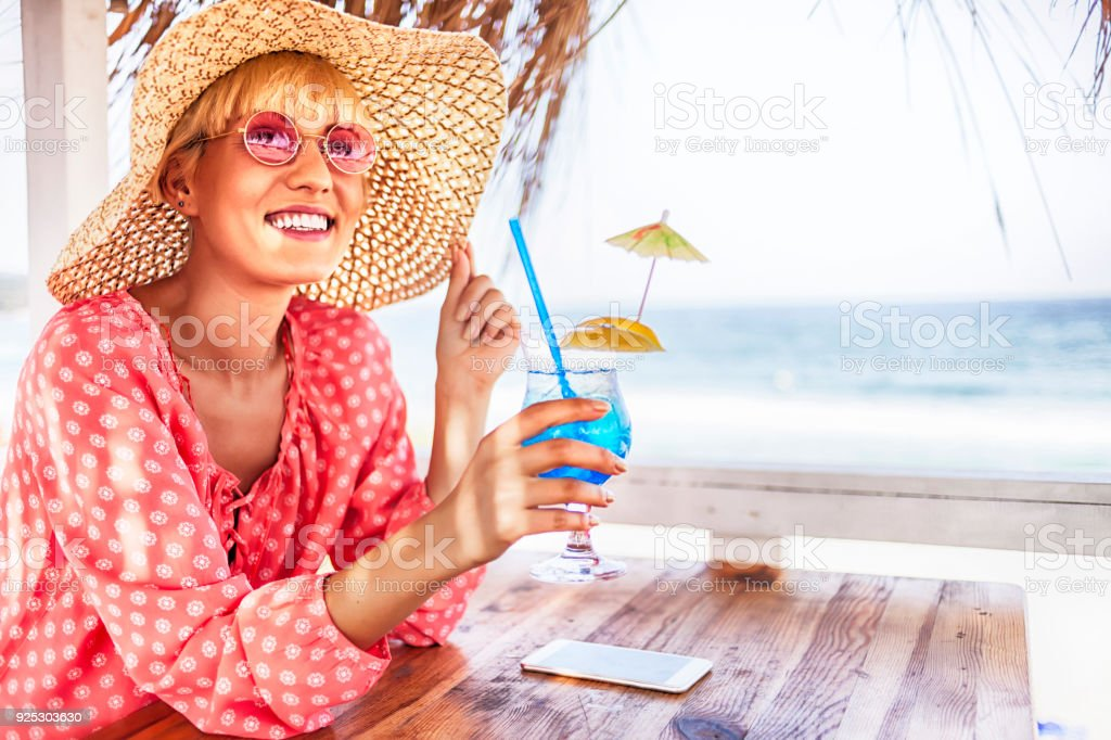 Blond woman drinking blue cocktail stock photo